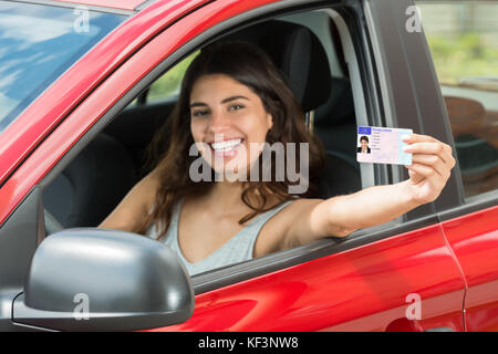 Smiling Young Woman Showing Her Driving License From Open Car Window - Stock Photo