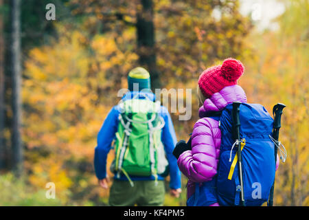 Happy couple hikers trekking in beautiful yellow autumn forest and mountains. Young people man and woman walking - Stock Photo
