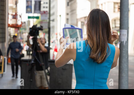 San Francisco, USA -  September 13th, 2017: A female TV reporter is looking her mirror before broadcast at a corner - Stock Photo