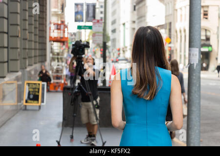 San Francisco, USA -  September 13th, 2017: An asian female TV reporter is looking ready to broadcast at a corner - Stock Photo