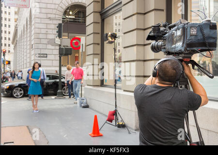San Francisco, USA -  September 13th, 2017: A male professional cameraman is broadcasting a female journalist at - Stock Photo