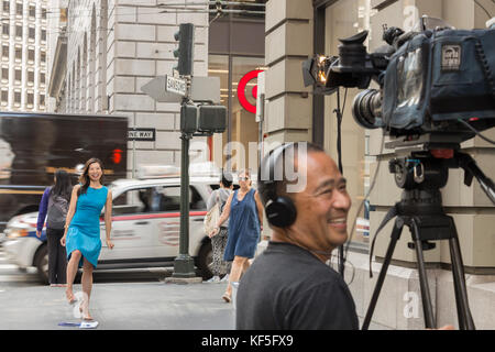 San Francisco, USA -  September 13th, 2017: A female asian TV reporter is laughing with the cameraman before broadcast. - Stock Photo