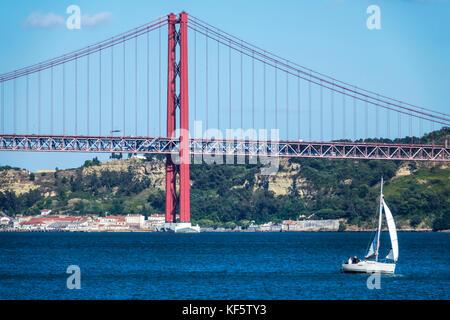 Lisbon Portugal Belem Tagus River Ponte 25 de Abril 25th of April Bridge suspension tower sailboat sailing view - Stock Photo