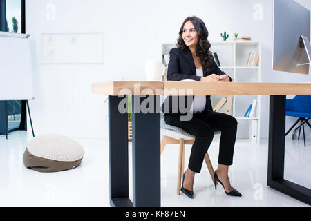 pregnant businesswoman sitting at workplace - Stock Photo