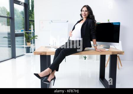 pregnant businesswoman sitting on worktable - Stock Photo