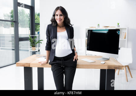 pregnant businesswoman leaning back on worktable - Stock Photo