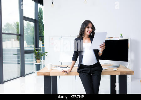 pregnant businesswoman with paperwork - Stock Photo