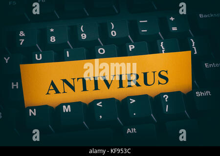 Yellow paper note on black keyboard with writing Antivirus. Close up. - Stock Photo