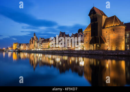 Scenic view of the lit Crane and other old buildings along the Long Bridge waterfront at the Main Town in Gdansk, - Stock Photo