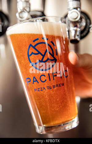 USA, Oregon, Bend, Pacific Pizza and Brew, pouring a pint glass of beer - Stock Photo