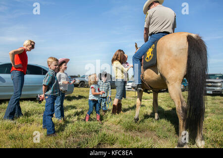USA, Oregon, Sisters, Sisters Rodeo, young kids meet and pet the Sheriff's horse - Stock Photo