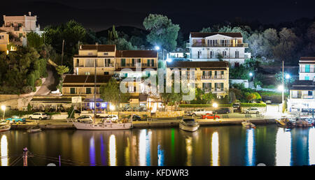 The bay, marina and harbor of Kassiopi as seen from above in the night. Colorful water reflections. Corfu, Greece. - Stock Photo