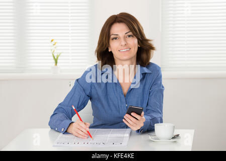 Young Woman Reading Classifieds On Newspaper With Smart Phone In Hand - Stock Photo