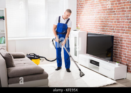 Smiling Young Male Janitor Vacuuming Carpet At Home - Stock Photo