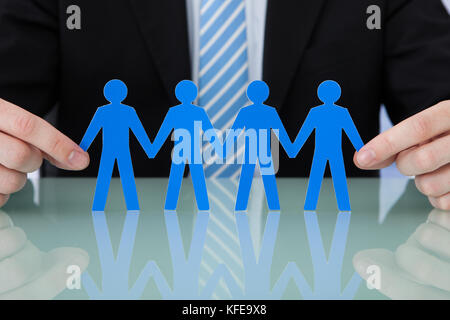 Midsection of young businessman holding blue paper people chain at office desk - Stock Photo