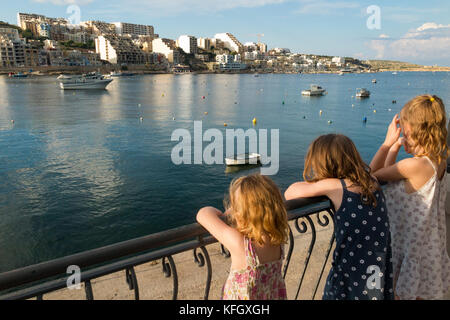 Three young sisters / girls / children / kids / kid look over St. Paul's Bay / St Paul 's Bay / Xemxija Bay, in - Stock Photo