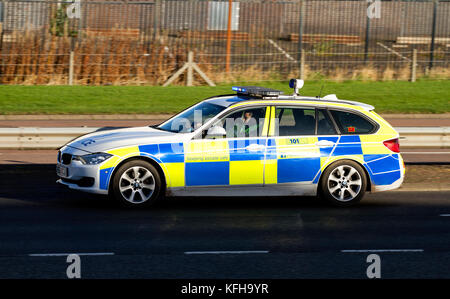 A Police Scotland BMW Police car with blue lights flashing speeding along the dual carriageway responding to a 999 - Stock Photo