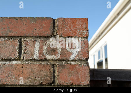 House number 109 sign painted on wall - Stock Photo