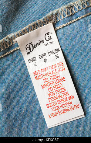 Keep away from fire label in many different languages in Denim Co top - Stock Photo