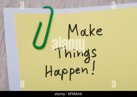 Closeup of Make Things Happen ! written on yellow paper note with paperclip - Stock Photo