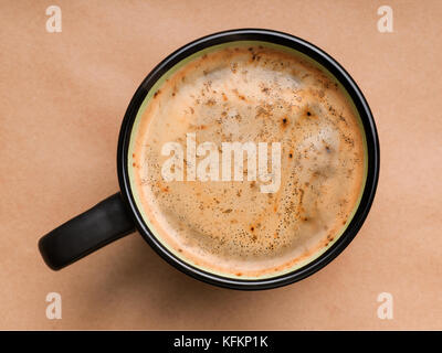 Coffee foam in black cup top view. On brown craft paper background - Stock Photo