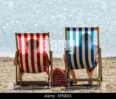 Two people sitting in deckchairs on the beach, photographed from behind, their shadows clear on the fabric - red - Stock Photo