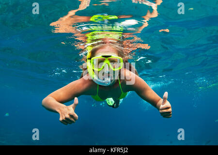 Happy family - girl in snorkeling mask dive underwater with tropical fishes in coral reef sea pool. Travel lifestyle, - Stock Photo