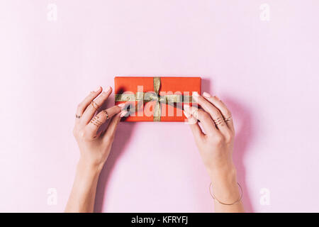 Top view of female hands tying a bow on a box with a gift on a pink background - Stock Photo