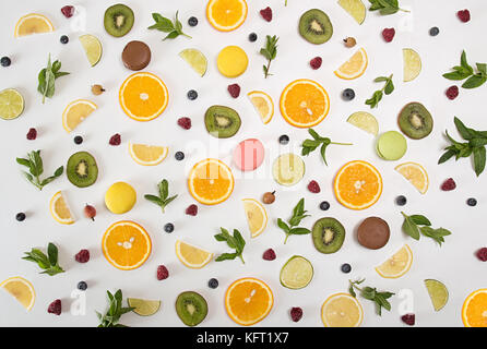 Flat lay still life with macarons, berries, mint and citrus and other fruits: orange fruit; lime; lemon, kiwi on - Stock Photo