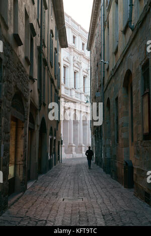 SILHOUETTE OF A MAN WALKING ON A DESERTED NARROW STREET. Città Alta (Upper City), Bergamo, Lombardy, Italy. - Stock Photo