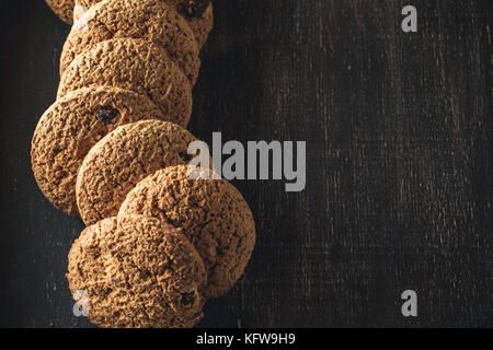 Oat cookies on brown rustic wooden background with space for your text - Stock Photo