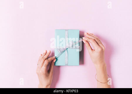 Top view of female hands tying a bow on a blue gift box - Stock Photo