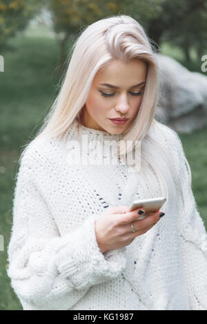 Portrait of young caucasian blonde hair woman in white pullover uses the phone outdoor. - Stock Photo