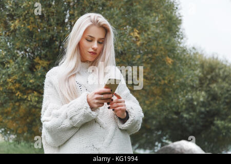 Portrait of young caucasian blonde hair woman in white pullover uses the phone outdoor - Stock Photo