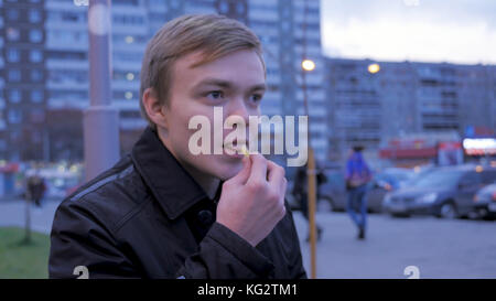 Guy eats fries potato on the street, on the bench. Man eating french fries, fried potato, chip, unhealthy junk fast - Stock Photo