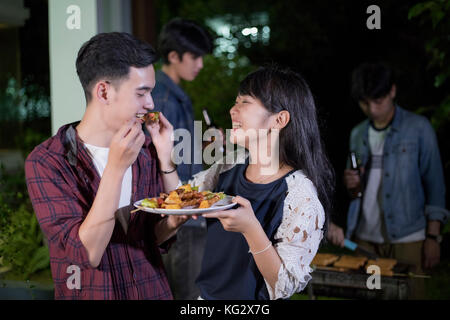 Asian young couple enjoying a romantic dinner and  group of friends having outdoor garden barbecue laughing with - Stock Photo