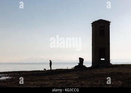A man walking a dog on a lake shore, beneath a big, empty sky, and near an old tower - Stock Photo