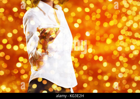christmas theme, woman drinks a glass of sparkling wine on blurred bright lights background, banner template with - Stock Photo