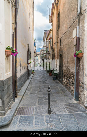 Typical traditional Sicilian lane with tall houses, basalt paving slabs and flowers - Stock Photo