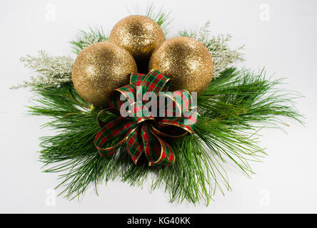 Three gold ornaments and 2 gold snowflakes on a bed of White Pine boughs along with a handmade bow of red and green - Stock Photo