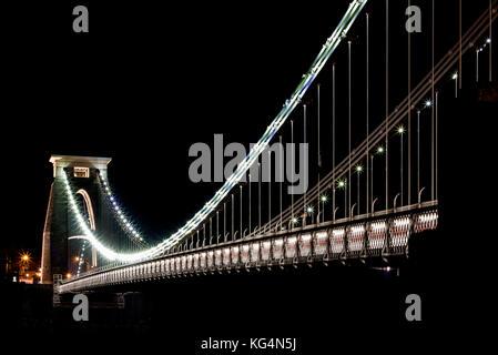 The Bristol Clifton Suspension Bridge illuminated at night. Designed by Isambard Kingdom Brunel to span the Avon - Stock Photo