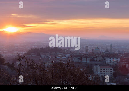 View of the medieval old town called Città Alta on hilltop framed by the fiery orange sky at dawn Bergamo Lombardy - Stock Photo