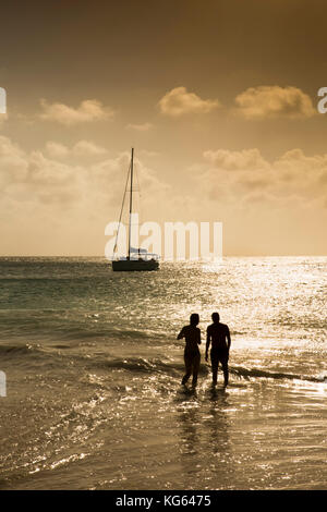 The Seychelles, Praslin, Anse Georgette, beach couple silhouetted in sea at sunset - Stock Photo