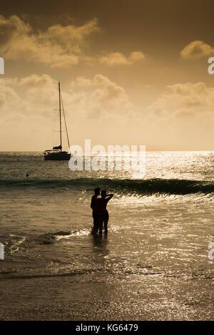 The Seychelles, Praslin, Anse Georgette beach, couple silhouette in sea at sunset - Stock Photo