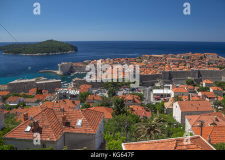Looking down on the old walled city of Dubrovnik and its  terracotta roofed buildings with Lokrun Island a short - Stock Photo