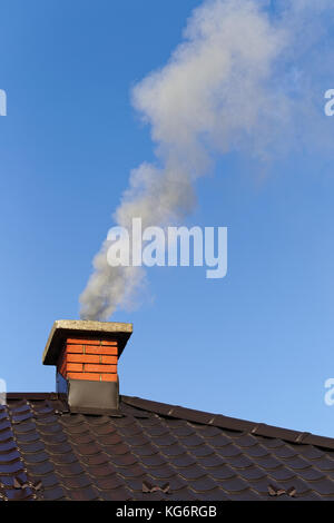 Smoke from brick chimney on the roof against the blue sky - Stock Photo