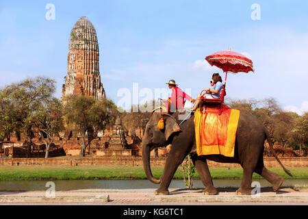 tourists take an elephant ride around Ayutthaya historic Park world heritage at Wat Phra Ram, Ayutthaya, Thailand - Stock Photo