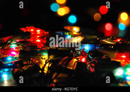 Christmas glowing electric garland with lights on a bokeh  background - Stock Photo