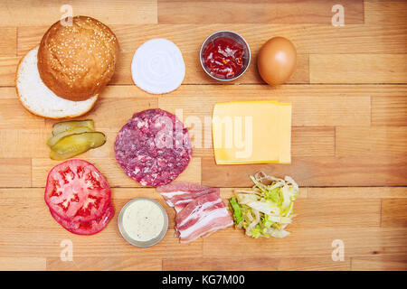 Ingredients for cooking burgers. Raw ground beef meat cutlet, onion, tomatoes, lettuce, pickles, sauces, cheese, - Stock Photo