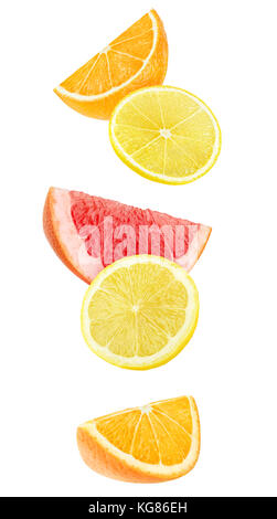 Isolated slices of citrus fruits. Falling pieces of orange, lemon and grapefruit isolated on white background with - Stock Photo